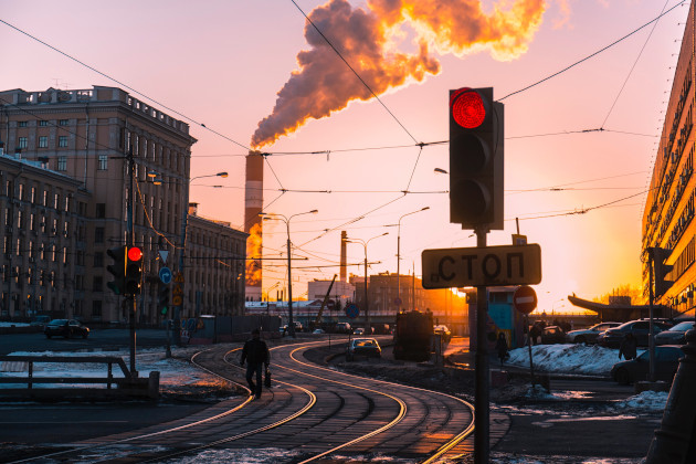 Road in Russian city, with power plant in the background and a stop sign in the foreground.